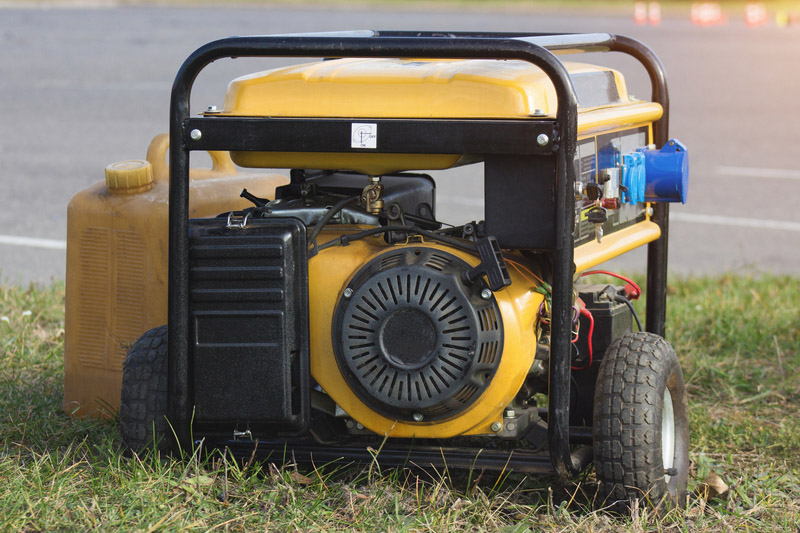 yellow petrol portable generator on wheels, close-up, alternator