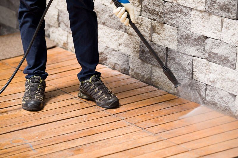 Close up of a man cleaning terrace with a power washer