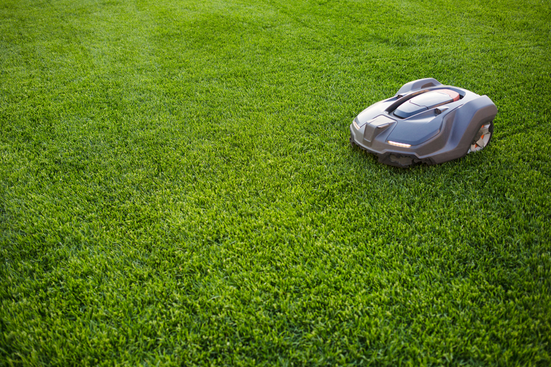 automatic lawn mower robot moves on the grass, lawn. side view from above, copy space.